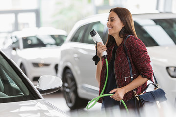 Smiling female customer carrying hybrid charging cable in car dealership showroom