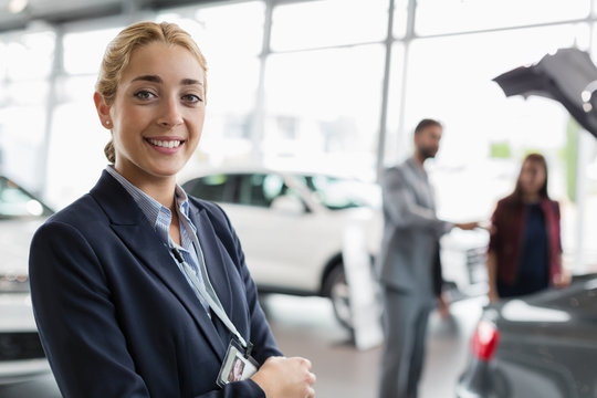 Portrait smiling, confident car saleswoman in car dealership showroom
