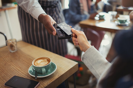 Customer credit card paying worker contactless payment in cafe