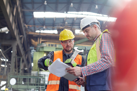 Male foreman and worker with clipboard talking in factory