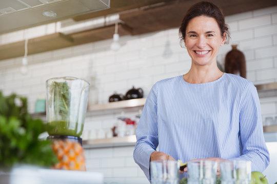 Portrait smiling, confident brunette woman preparing healthy green smoothie in blender in kitchen