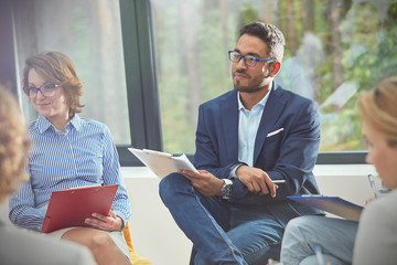 Attentive man with clipboard listening in group therapy session