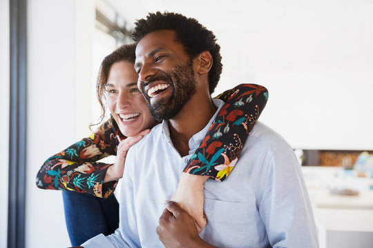 Laughing, affectionate multi-ethnic couple looking away