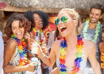 Playful friends wearing leis drinking and partying at sunny summer poolside