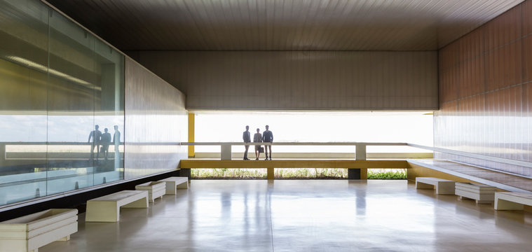 Business people on elevated walkway in modern office lobby