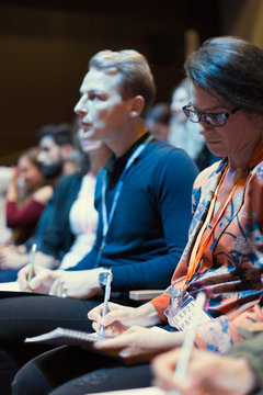 Attentive businesswoman taking in notes in conference audience