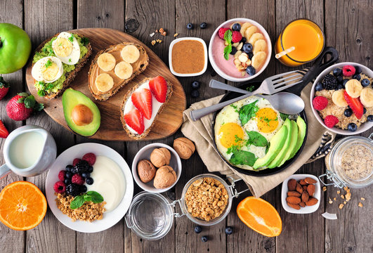 Healthy breakfast table scene with fruit, yogurts, oatmeal, smoothie, nutritious toasts and egg skillet. Top view over a wood background.