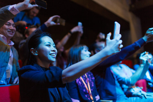 Smiling, enthusiastic woman using camera phone in dark audience