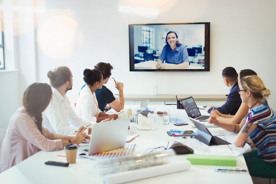Designers video conferencing in conference room meeting