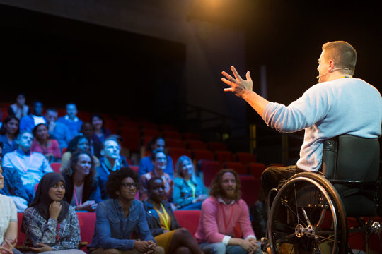 Speaker in wheelchair on stage talking to conference audience