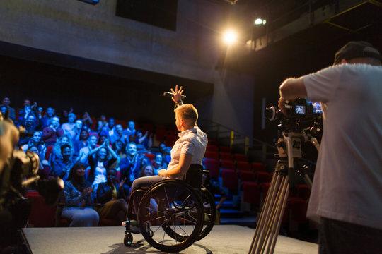 Female speaker in wheelchair on stage waving to audience