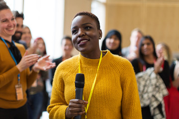 Smiling businesswoman speaker with microphone at conference