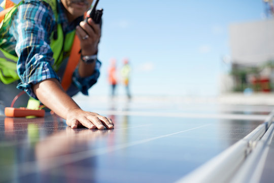 Engineer with walkie-talkie inspecting solar panels at power plant