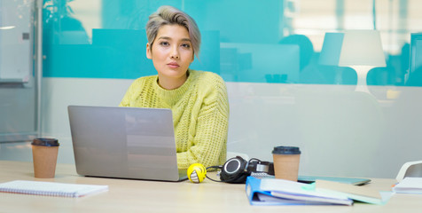 Portrait confident, determined young businesswoman working at laptop