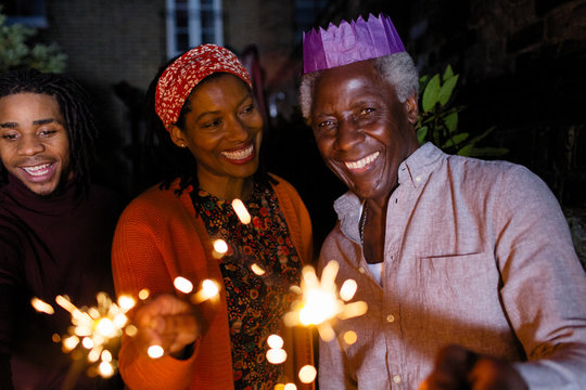 Portrait smiling senior father sparklers in paper crown celebrating daughter
