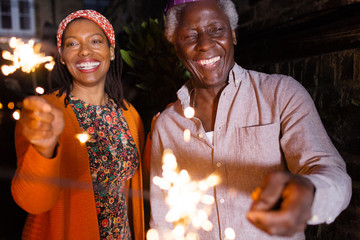 Portrait happy senior father and daughter celebrating with sparklers