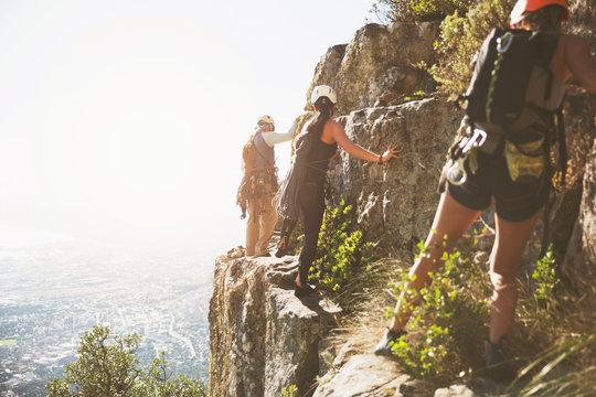 Rock climbers climbing rocks above sunny ocean