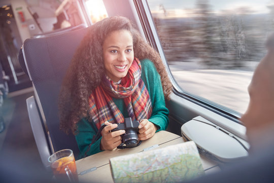 Smiling young woman with camera and map riding passenger train