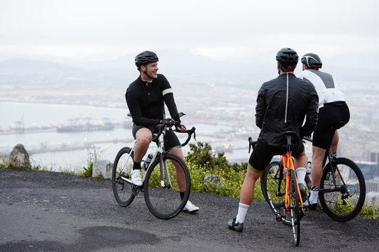 Male cyclist friends taking a break at overlook