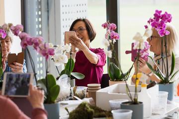 Active seniors with camera phones enjoying flower arranging class