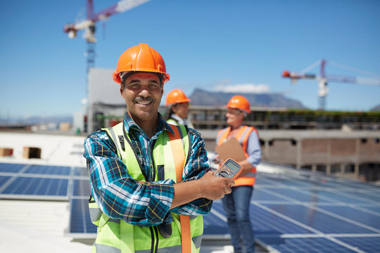 Portrait confident engineer installing solar panels on sunny rooftop