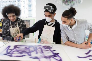 Teenage boys spray painting in high school art class