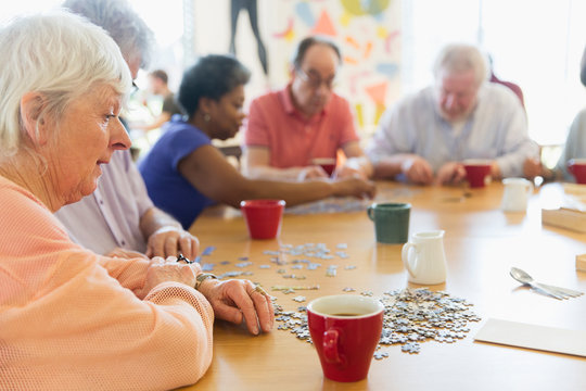 Senior woman assembling jigsaw puzzle friends at table in community center