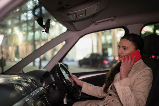 Businesswoman talking on smart phone in car at night
