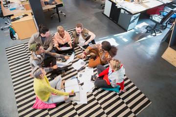 Creative business team meeting, brainstorming in circle on floor in office