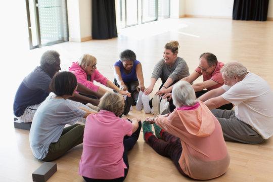 Active seniors exercising, stretching legs in circle