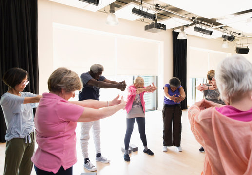 Active seniors exercising, stretching arms and back in circle