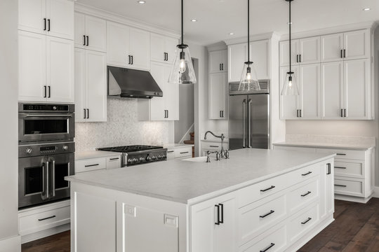Beautiful kitchen in new luxury home with stainless steel appliances, pendant lights, and hardwood floors