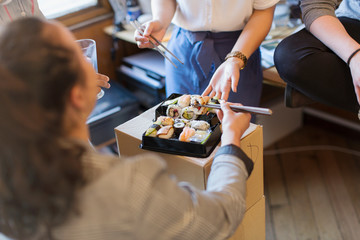Business people eating sushi in office