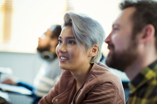 Smiling creative businesswoman listening in meeting
