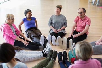 Instructor active seniors stretching legs in circle in exercise class