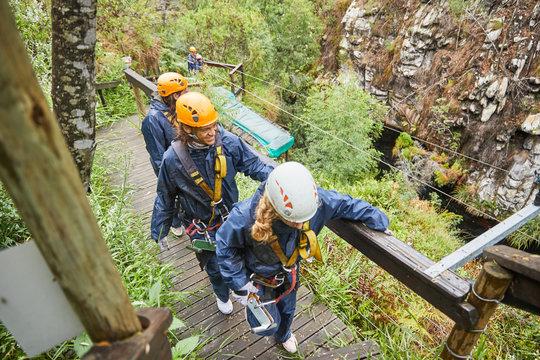 Friends walking on bridge, preparing to zip line