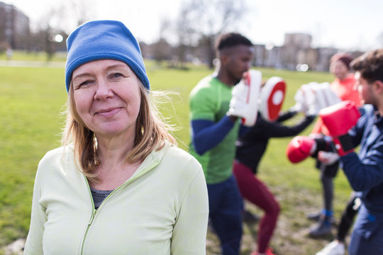 Portrait confident senior woman boxing in park