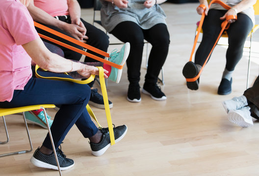 Active seniors stretching, exercising with straps