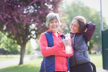 Portrait confident active senior female runner friends drinking water in park