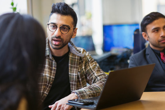 Businessman at laptop talking with colleague