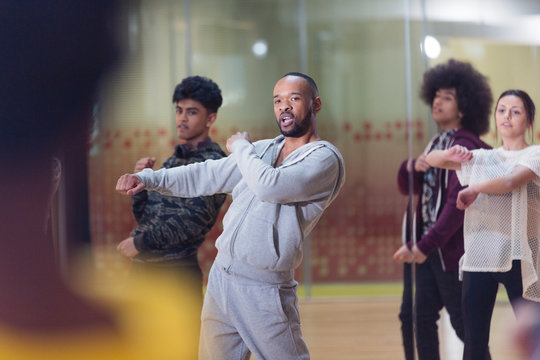 Male instructor leading dance class in studio