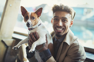 Portrait smiling young man holding dog