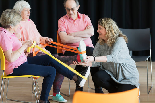 Instructor helping active seniors stretching legs, exercising straps