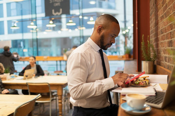 Businessman using smart phone and eating lunch in cafe