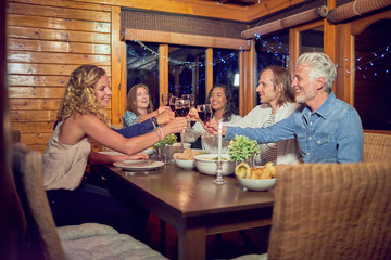 Friends toasting red wine glasses, enjoying dinner at cabin dining room table