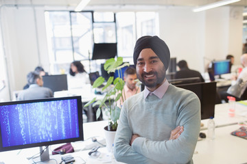 Portrait smiling, confident Indian computer programmer in turban in office