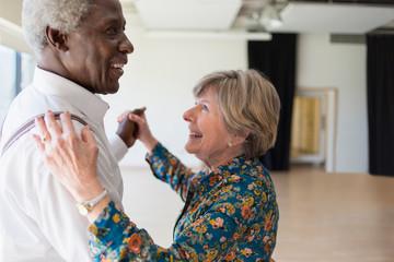 Happy active senior couple dancing in dance studio