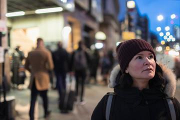 Woman in warm clothing standing on urban sidewalk at night
