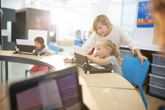 Teacher and student using laptop