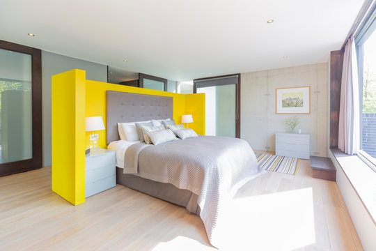 Modern bedroom with yellow and gray headboard